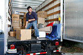 Young man unloading box in moving van