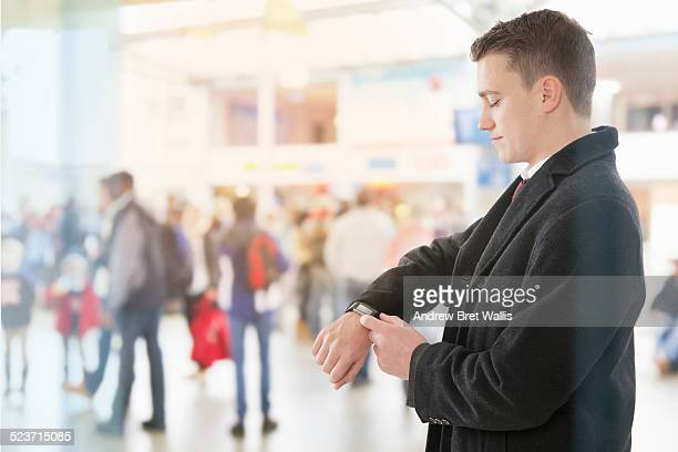 Young man uses a smart watch at the airport