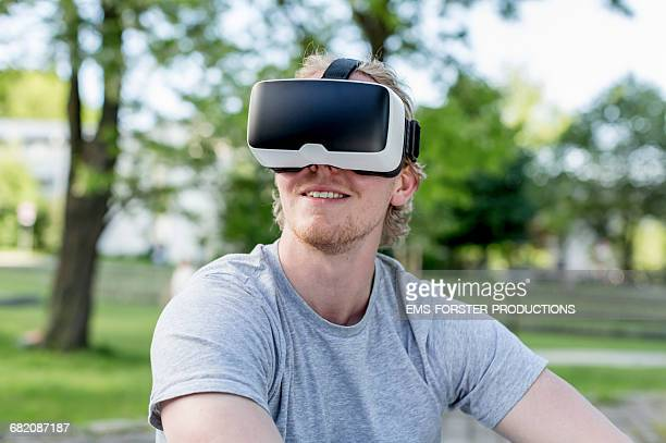 young man uses VR head set outside