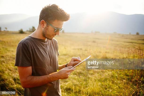 Junger Mann mit digitalen tablet im Freien