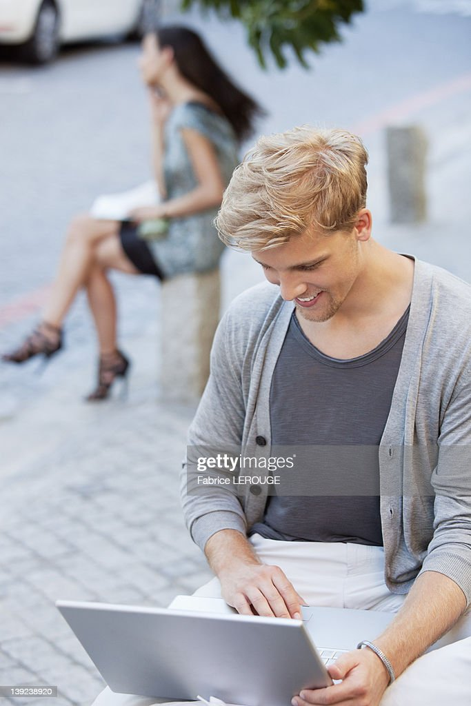 Young man using a laptop with a woman in the background on a street : Stock Photo