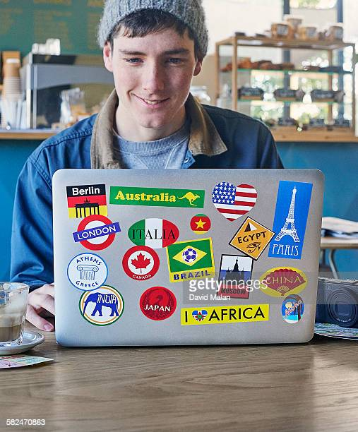 Young man using a laptop with travel stickers