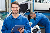 Smiling mechanic using a tablet pc at the repair garage
