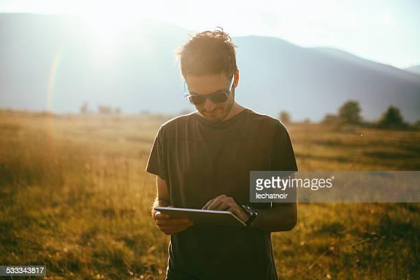 Junger Mann mit einem tablet im Freien