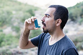 Young man using an asthma inhaler