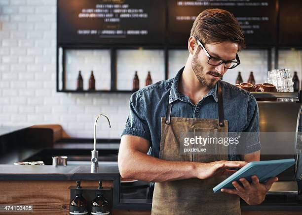 Young man using blue tablet in a cafe
