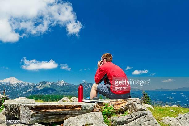 Junger Mann mit Handy in die Berge