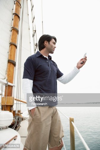 Young man using cellular telephones in sailboat