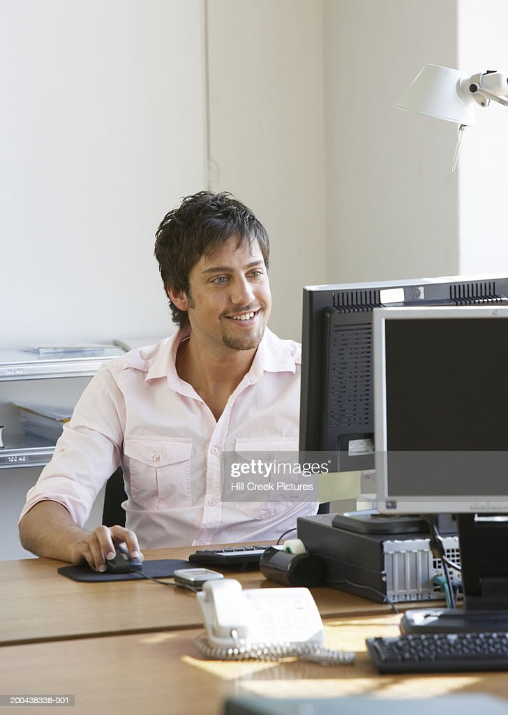 Young man using computer at desk, smiling : Stock Photo