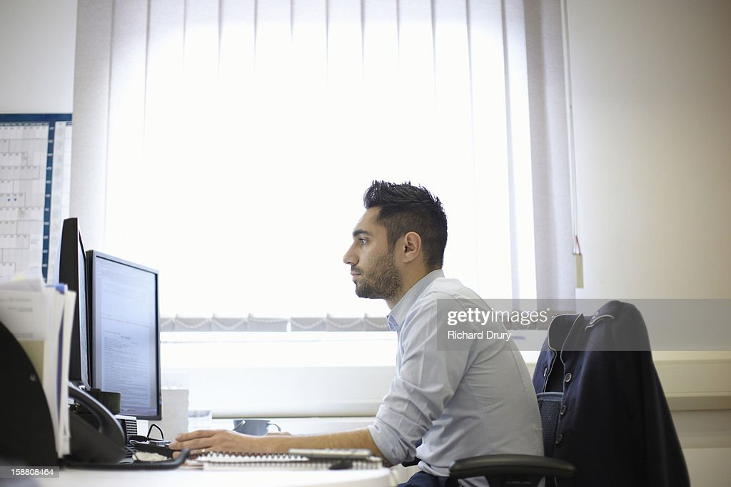 Young man using computer in office : Stock Photo