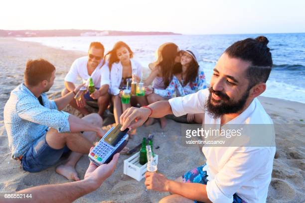 Young man using credit card for contactless payment on beach