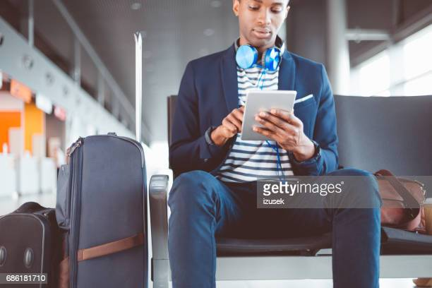 Young man using digital tablet at airport lounge