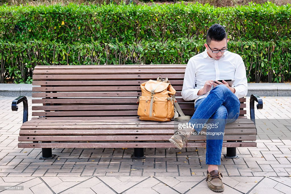 Young man using digital tablet in park.