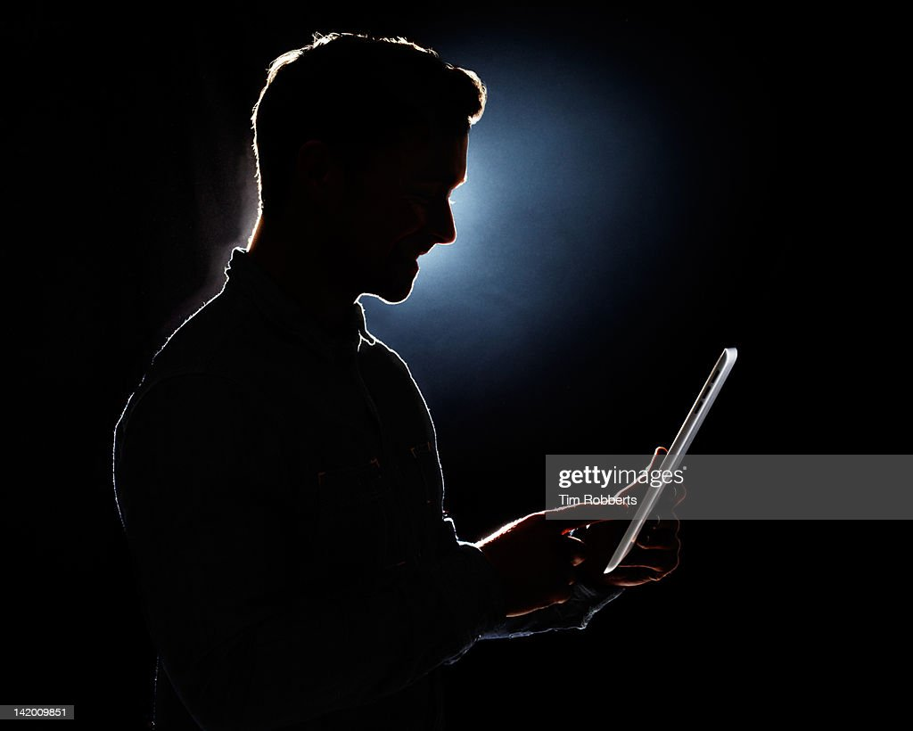 Young Man Using Digital Tablet In Silhouette Stock Photo ...