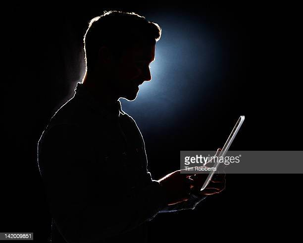 Young man using digital tablet in silhouette.