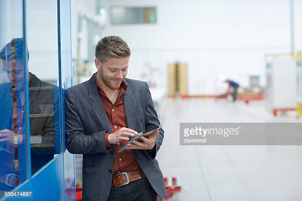 Young man using digital tablet on factory shopfloor