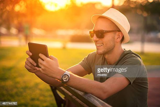 Young man using digital tablet outdoors at sunset