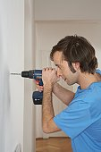 Young man using drill at wall, side view