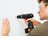 Young man using electric drill