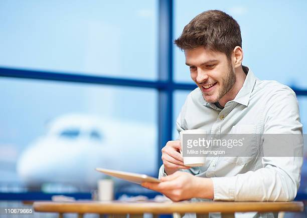 Young Man Using Graphics Tablet In Airport Cafe