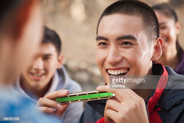 Young man using harmonica, portrait