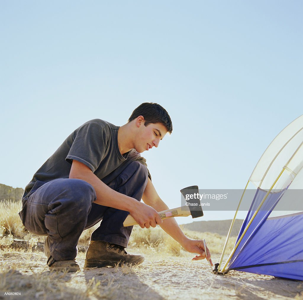 Young man using hatchet to pound tent peg into ground, side view