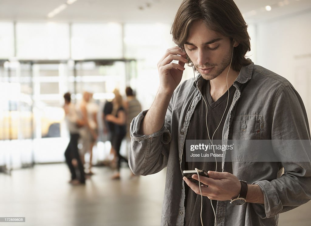 Young man using his smart phone colleagues in back : Stock Photo