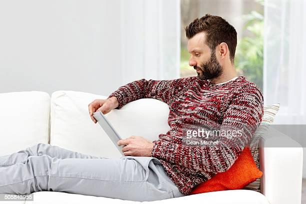 Giovane uomo usando il suo tablet a casa