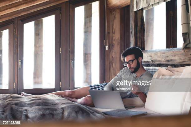 Young man using laptop and credit card lying in bed at home