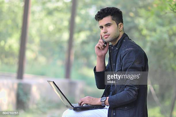 Young man using laptop and talking on phone