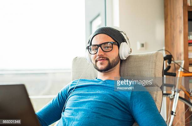 Young man using laptop and wearing headphones