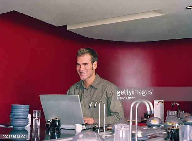 Young man using laptop computer in sushi restaurant, smiling