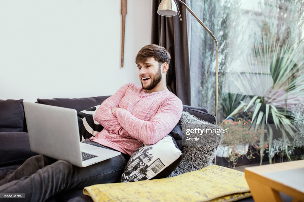 Young man using laptop, having video call with a friend : Stock Photo