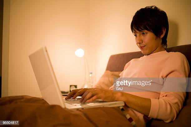 Young man using laptop in bed