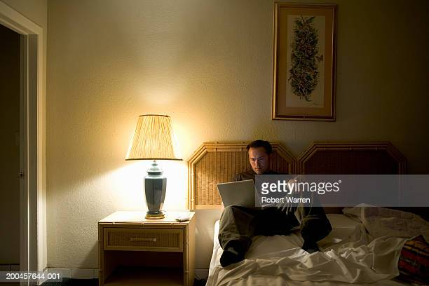 Young man using laptop in motel room, close-up