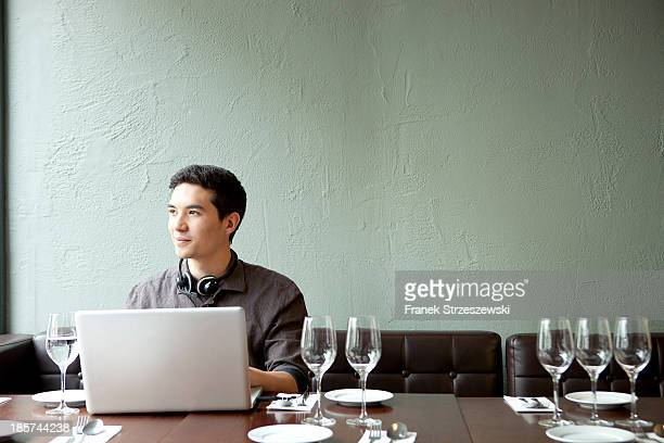 Young man using laptop in restaurant