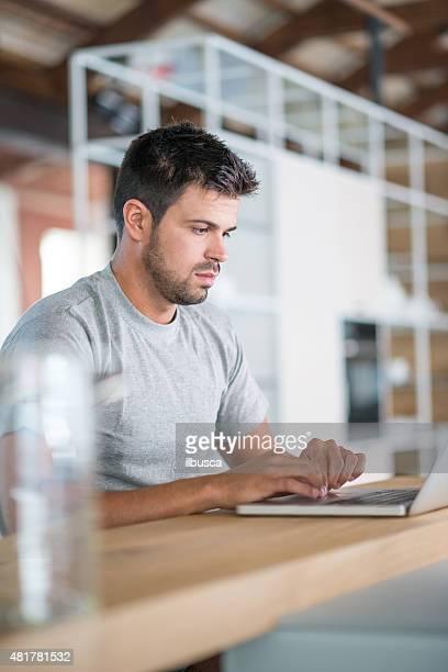 Junger Mann mit laptop in der Küche