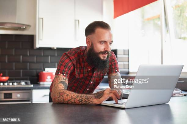 Young man using laptop on his kitchen