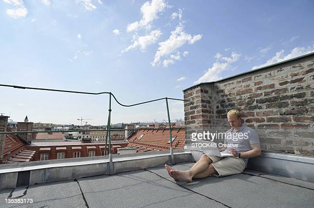 Young man using laptop on roof