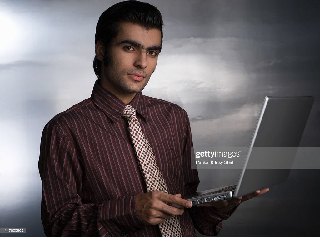 Young man using laptop, portrait : Stock Photo