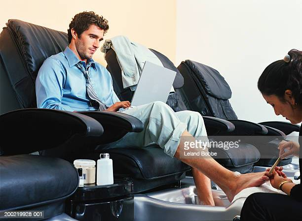 Young man using laptop, receiving pedicure at spa