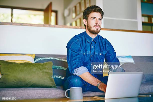 Young man using laptop while looking away at home
