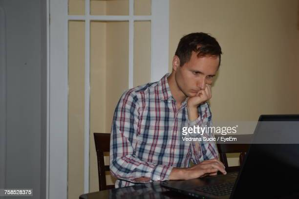 Young Man Using Laptop While Sitting At Home