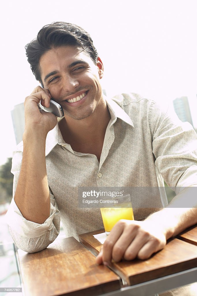Young man using mobile phone at outdoor table, smiling : Stock Photo
