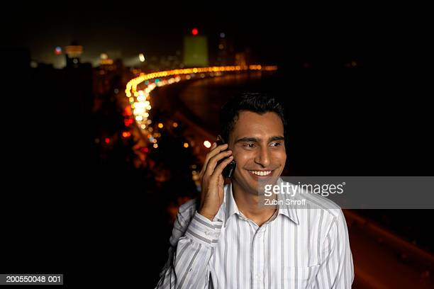 Young man using mobile phone, night