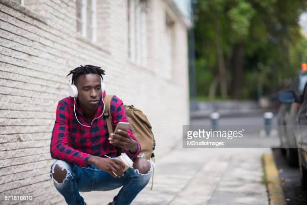 Ung man med hjälp av mobiltelefon