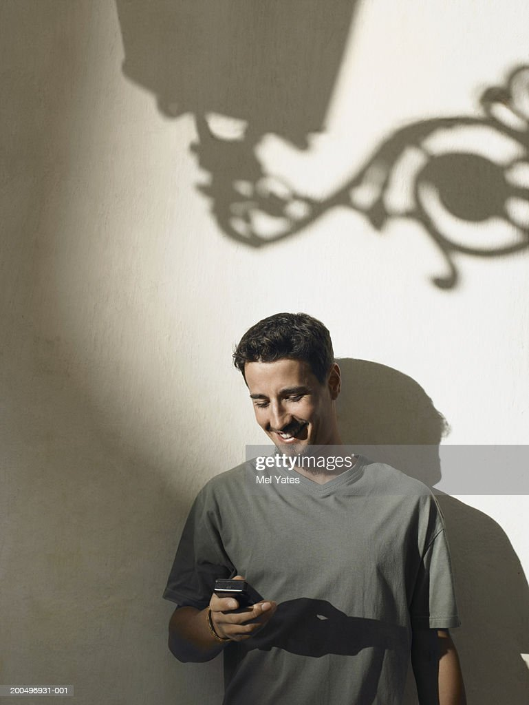 Young man using mobile phone, smiling : Stock Photo