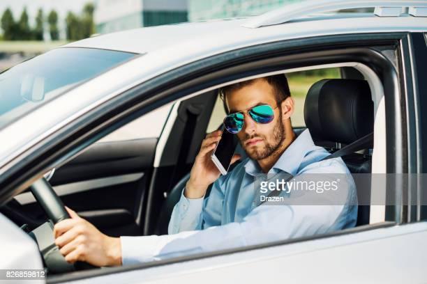 Jeune homme à l'aide de téléphone portable pendant la conduite contre les procédures de sécurité