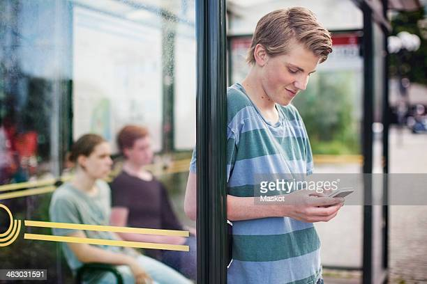 Young man using mobile phone while waiting with friends at bus stop