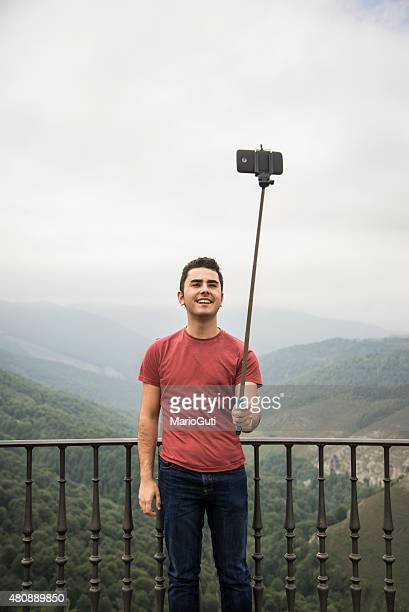 Young man using selfie stick